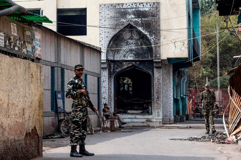 Security personnel stand guard outside of a burned mosque following communal violence in New Delhi on Feb. 28.