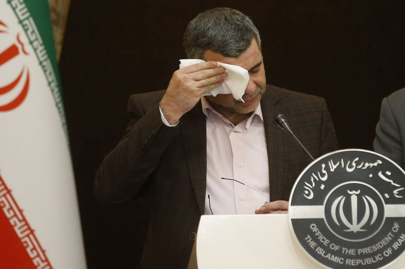 Iranian Deputy Health Minister Iraj Harirchi wipes the sweat off his face, during a press conference with the Islamic republic's government spokesman Ali Rabiei in Tehran on Feb. 24. He confirmed on Feb. 25 that he has tested positive for the novel coronavirus, amid a major outbreak in Iran.