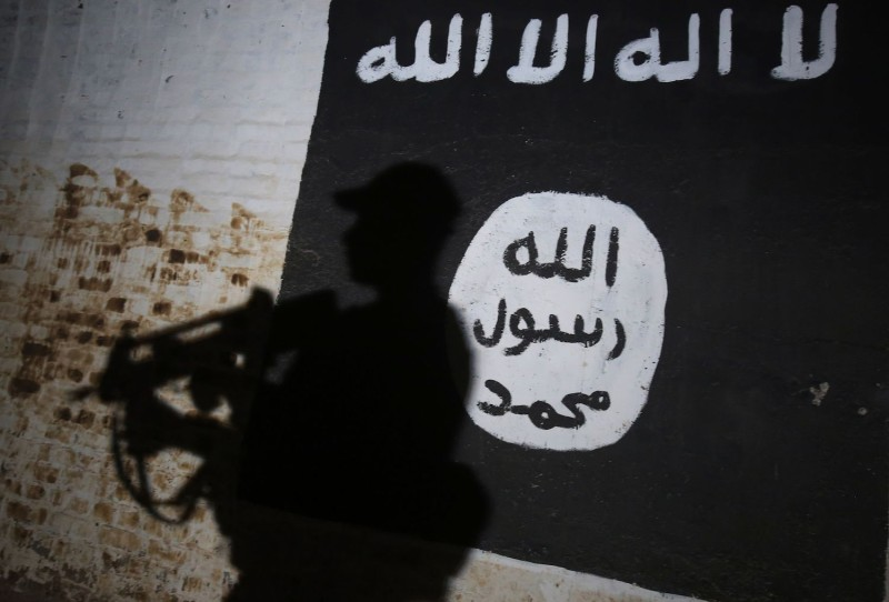 A member of the Iraqi forces walks past a mural bearing the flag of the Islamic State.