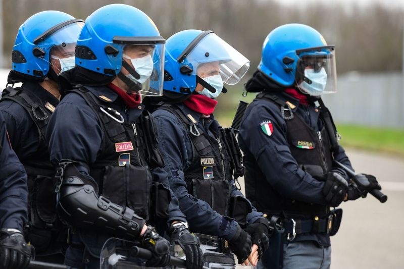 Anti-riot police officers wearing masks stand guard following a prison revolt at the Sant'Anna prison in Modena, Emilia-Romagna, in one of Italy's quarantine red zones on March 9.