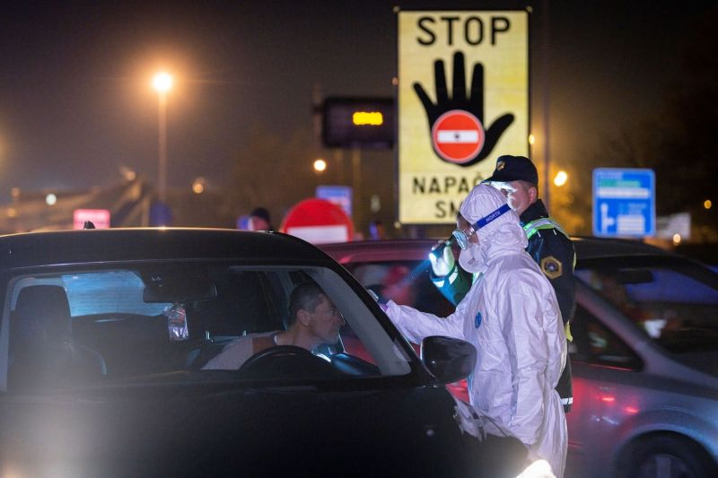 A medical worker measures body temperatures of motorists at the  Slovenian-Italian border crossing near Nova Gorica, Slovenia on March 11, after Slovenia's government announced it would close its border with Italy, hard hit by the outbreak of COVID-19.