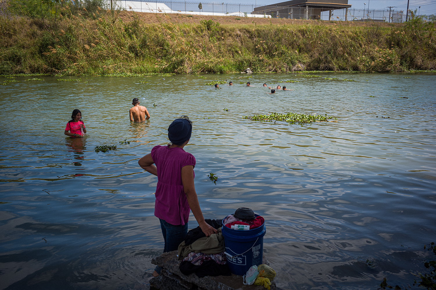 A mother looks out to her children as they swim in the Rio Grande, near Matamoros, while she does laundry March 18.