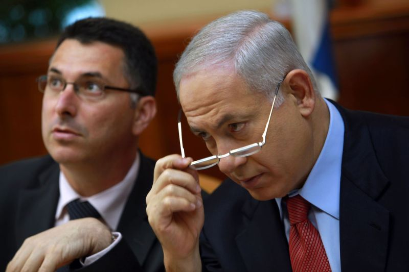 Israeli Prime Minister Benjamin Netanyahu looks over his glasses as he and Education Minister Gidon Saar chat at the start of the weekly cabinet meeting October 18, 2009 in Jerusalem.