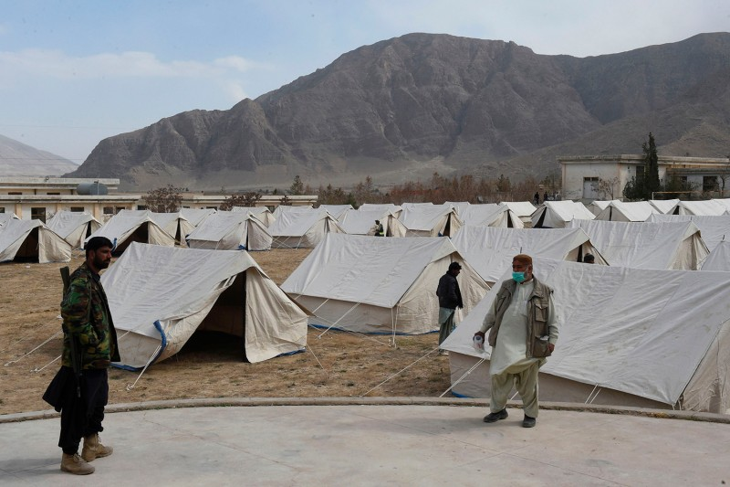 Workers from the Provincial Disaster Management Authority of Balochistan stand inside a COVID-19 quarantine camp for people returning from Iran via the border town of Taftan, on the outskirts of Quetta, Pakistan, on March 9.