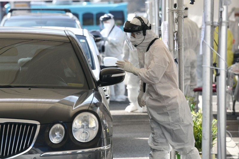Medical workers wearing protective gear take samples from a driver with suspected symptoms of coronavirus at a test facility in Goyang, north of Seoul, on Feb. 29.