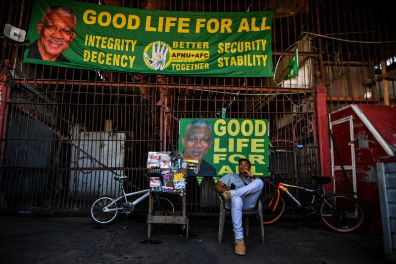 A street vendor sits next to banners of the presidential candidate for the National Unity and Alliance for Change party (APNU+AFC) David Granger, in Georgetown, Guyana, on March 1, 2020.
