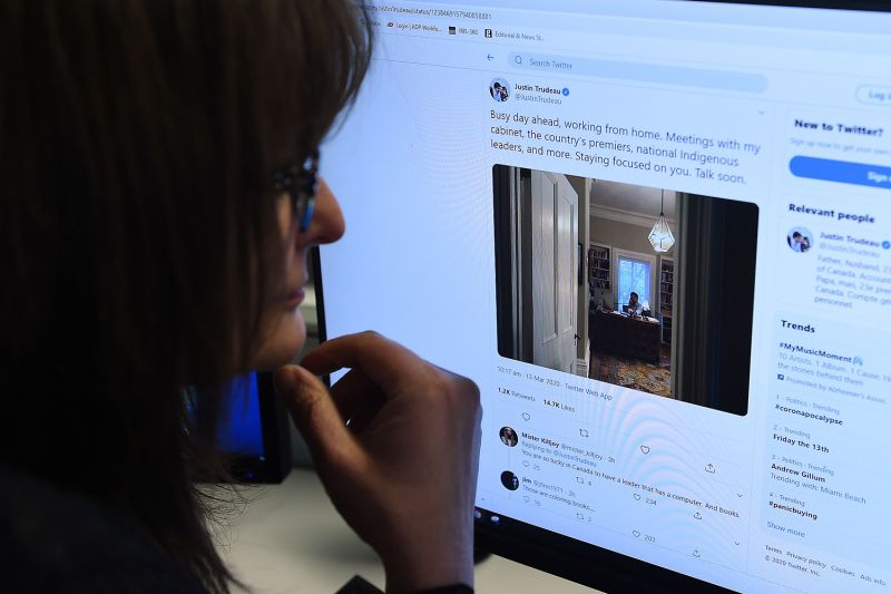 An editor looks at the Twitter account of Canadian Prime Minister Justin Trudeau showing a picture of him in self-isolation after his wife tested positive for the coronavirus on March 13. OLIVIER DOULIERY/AFP via Getty Images