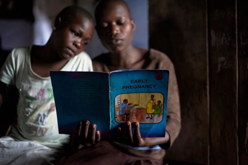 Girls read an educational book about family planning in Uganda