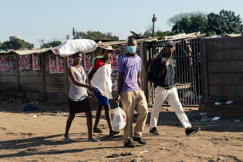 A man and his family walk past closed vegetable stalls.