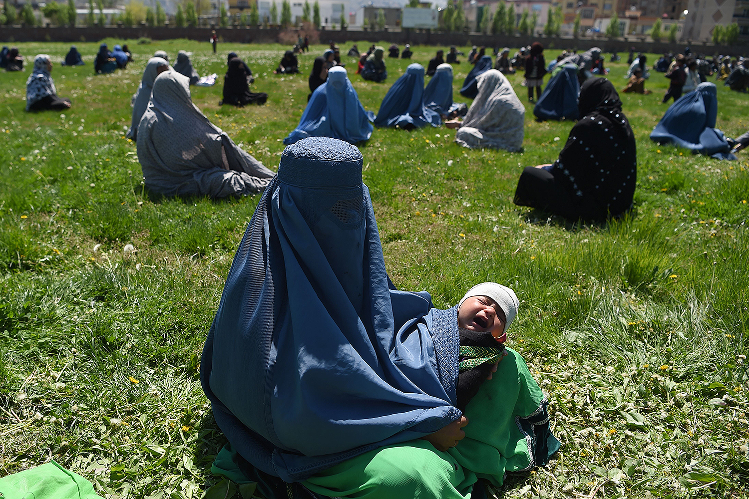 A woman holds her child as she waits to receive free wheat from the government emergency committee in Kabul, Afghanistan, on April 21. WAKIL KOHSAR/AFP via Getty Images