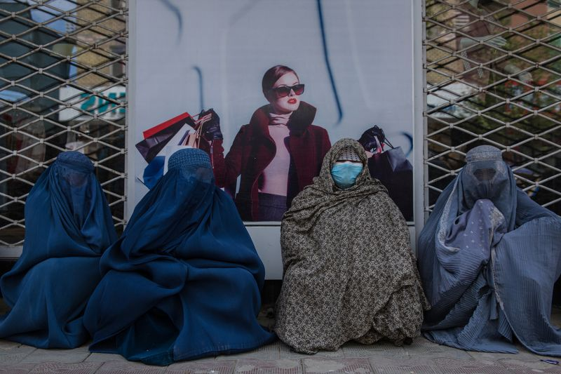 Faranaz Anwari, a 35-year-old widow with three children, wears a face mask as she sits on a Kabul street begging with other women on April 22.