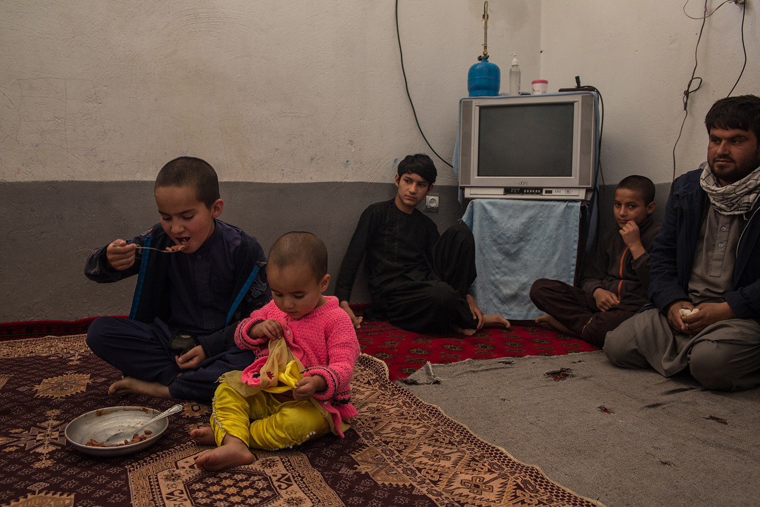 Asadullah Haidery (far right) and his children, seen in the room they rent on April 22, have recently had only beans to eat. The family lives in a basement room of a rented house, but can't afford the 2,000 Afghani ( USD) rent anymore.