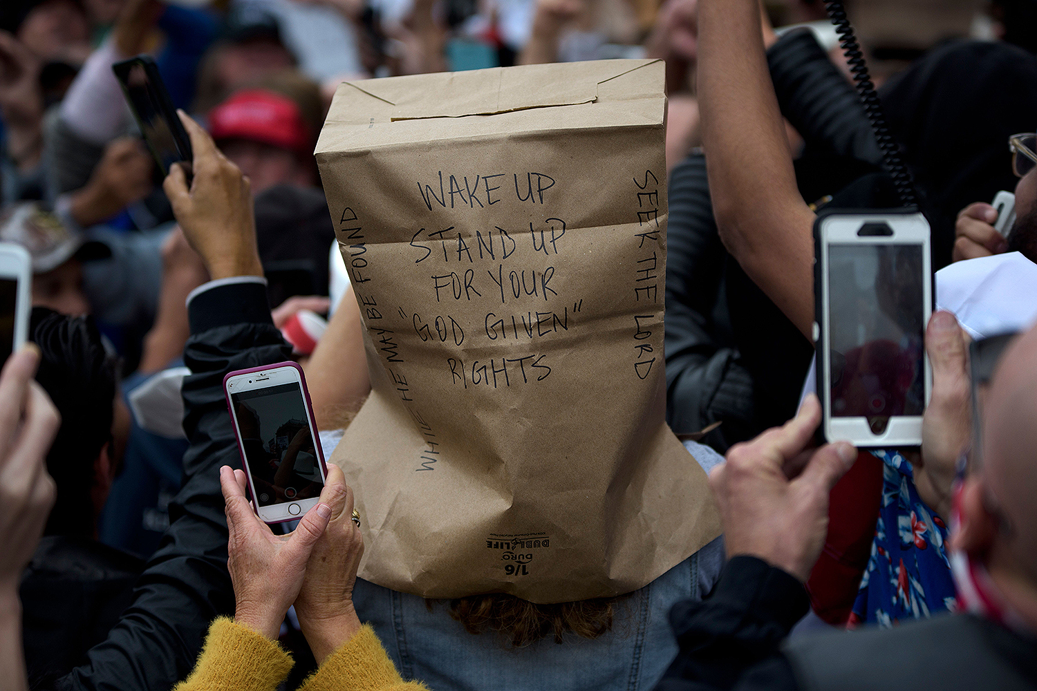 "A protester wears a bag over their head during a ""Reopen America"" rally at the state Capitol in Austin, Texas, on April 18. MARK FELIX/AFP /AFP via Getty Images"