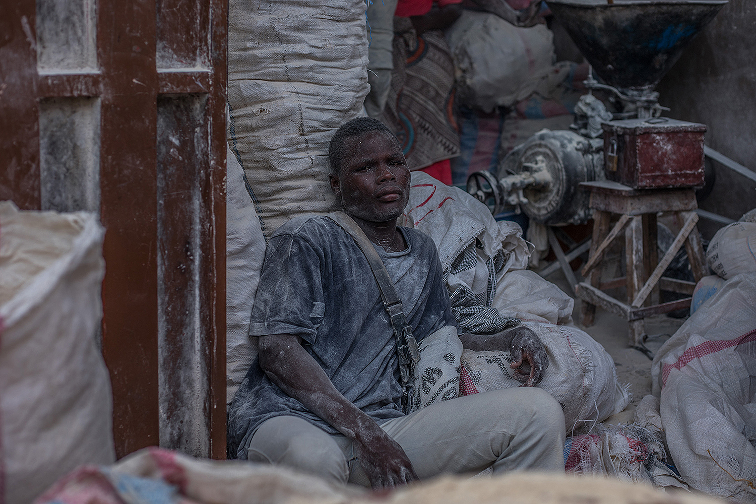 A miller rests after filling bags of flour at Benin's Dantokpa Market, the largest open-air market in West Africa, on April 20. YANICK FOLLY/AFP via Getty Images