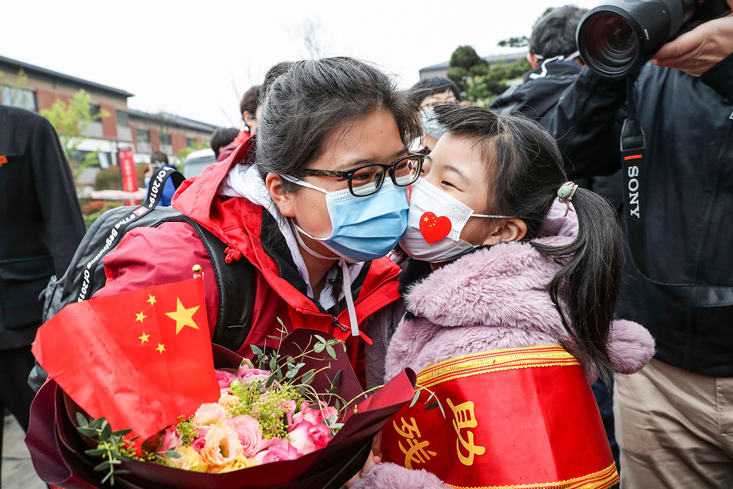 A member of a medical assistance team from Huai'an, China, is welcomed home by her daughter March 31 after working in Wuhan to help with the coronavirus recovery effort. STR/AFP via Getty Images