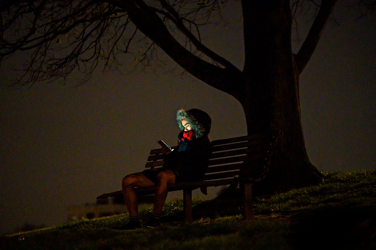 A man looks at his phone while resting on Primrose Hill in London on April 18. JUSTIN TALLIS/AFP via Getty Images