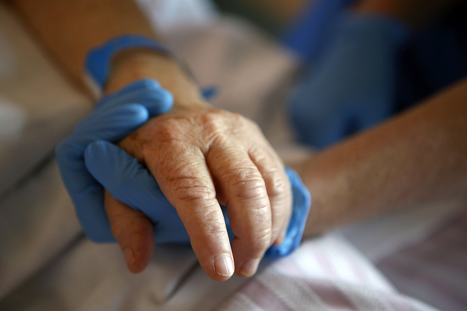 A nurse holds the hand of a patient in the palliative care unit of Eugenie Hospital in Ajaccio, on the French Mediterranean island of Corsica, on April 23. PASCAL POCHARD-CASABIANCA/AFP via Getty Images
