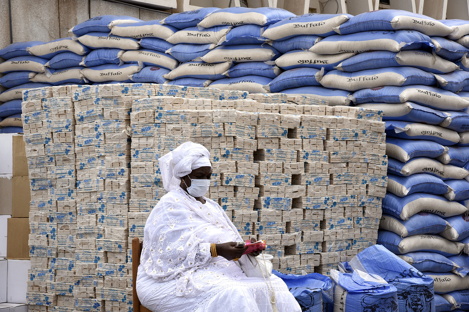 A municipal agent waits for bars of soap and bags of rice to be distributed to residents of the 19 municipalities in Dakar, Senegal, on April 10. SEYLLOU/AFP via Getty Images