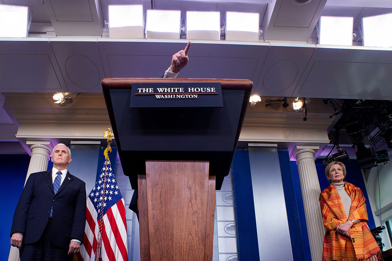 U.S. President Donald Trump gestures over the lectern as he speaks at a White House daily briefing April 3. He is flanked by Vice President Mike Pence and Deborah Birx, coordinator for the White House Coronavirus Task Force. JIM WATSON/AFP via Getty Images