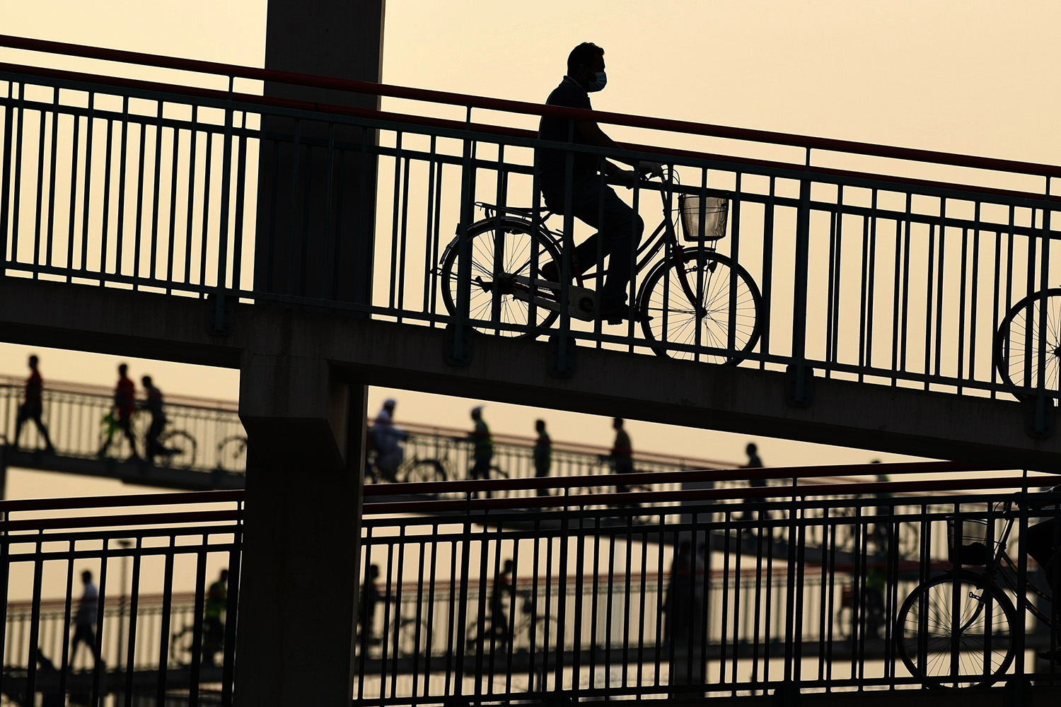 People walk or ride bicycles over a bridge in the Emirati city of Dubai on April 2. KARIM SAHIB/AFP via Getty Images