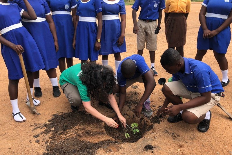 Mafalda Duarte (left), head of the Climate Investment Funds, plants cocoa seeds with students in Ghana in 2018.