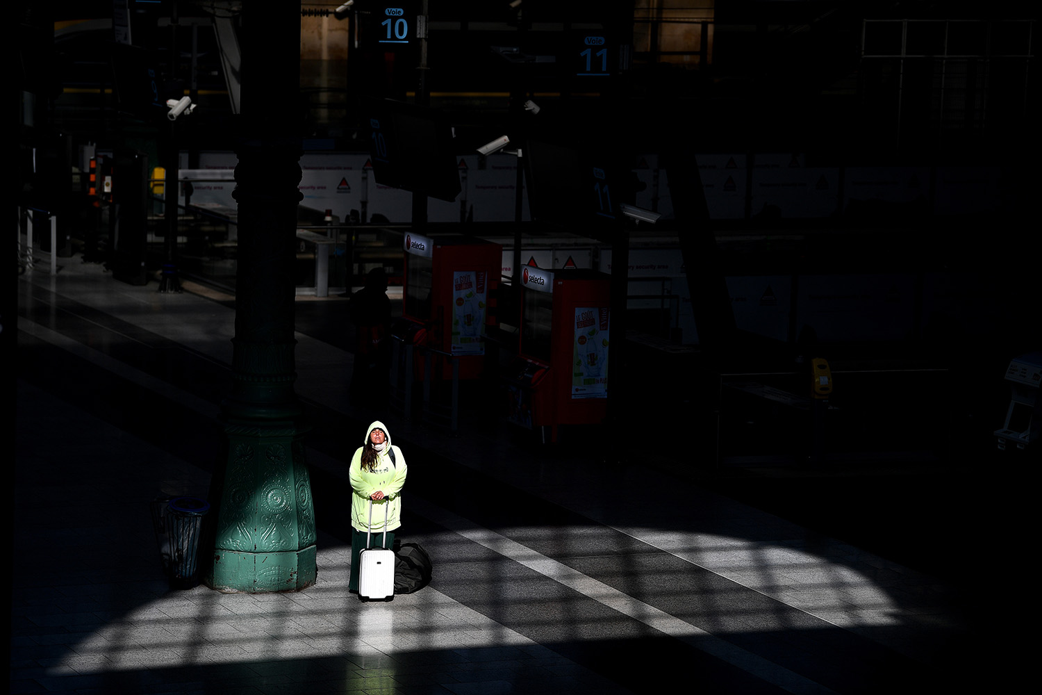 A woman waits with her suitcase at the Gare du Nord train station in Paris on April 1. FRANCK FIFE/AFP via Getty Images