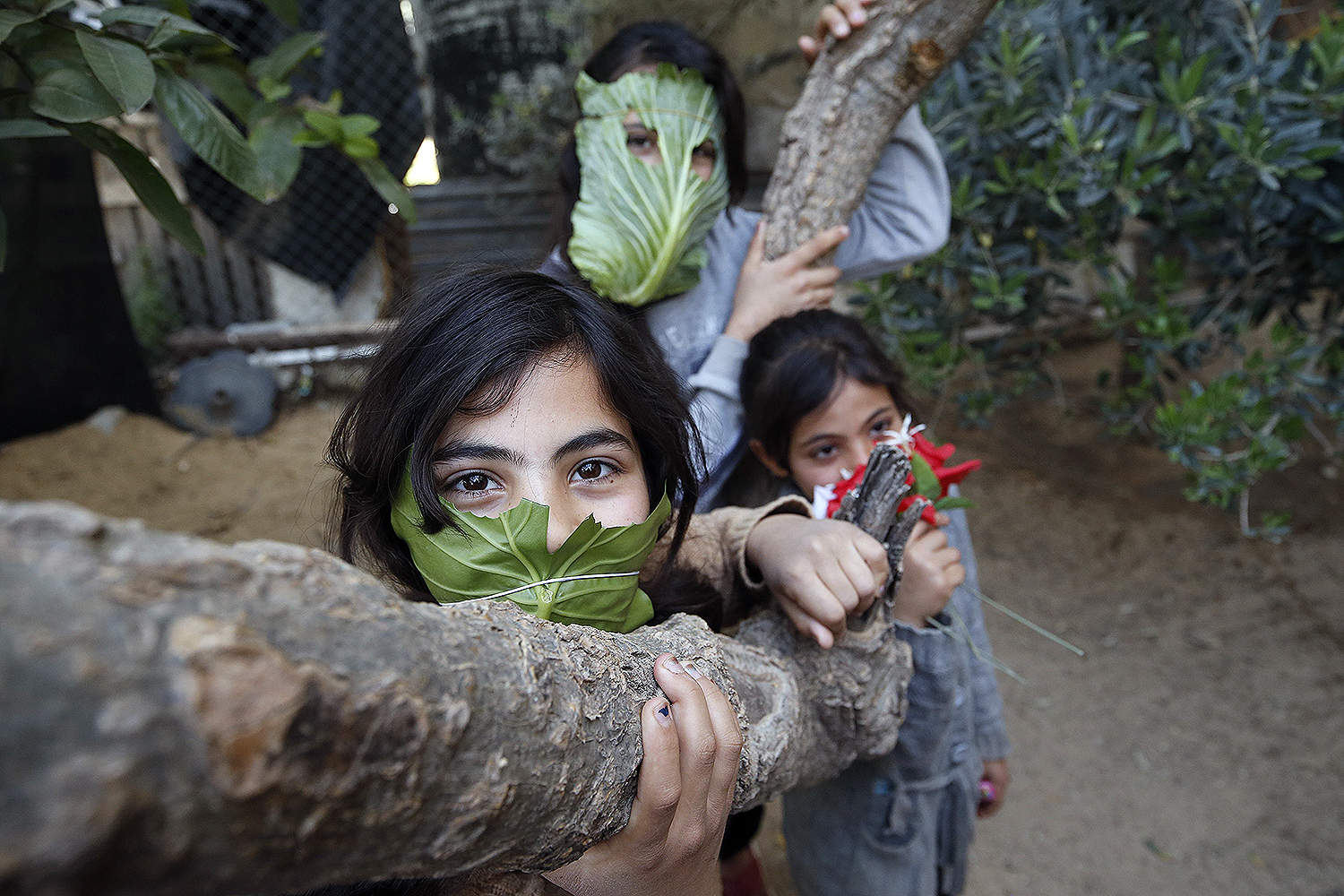 Amid the coronavirus pandemic, Palestinian children pose with makeshift masks made of cabbage while cooking at home with their family in Beit Lahia, a city in the Gaza Strip, on April 16. MOHAMMED ABED/AFP via Getty Images