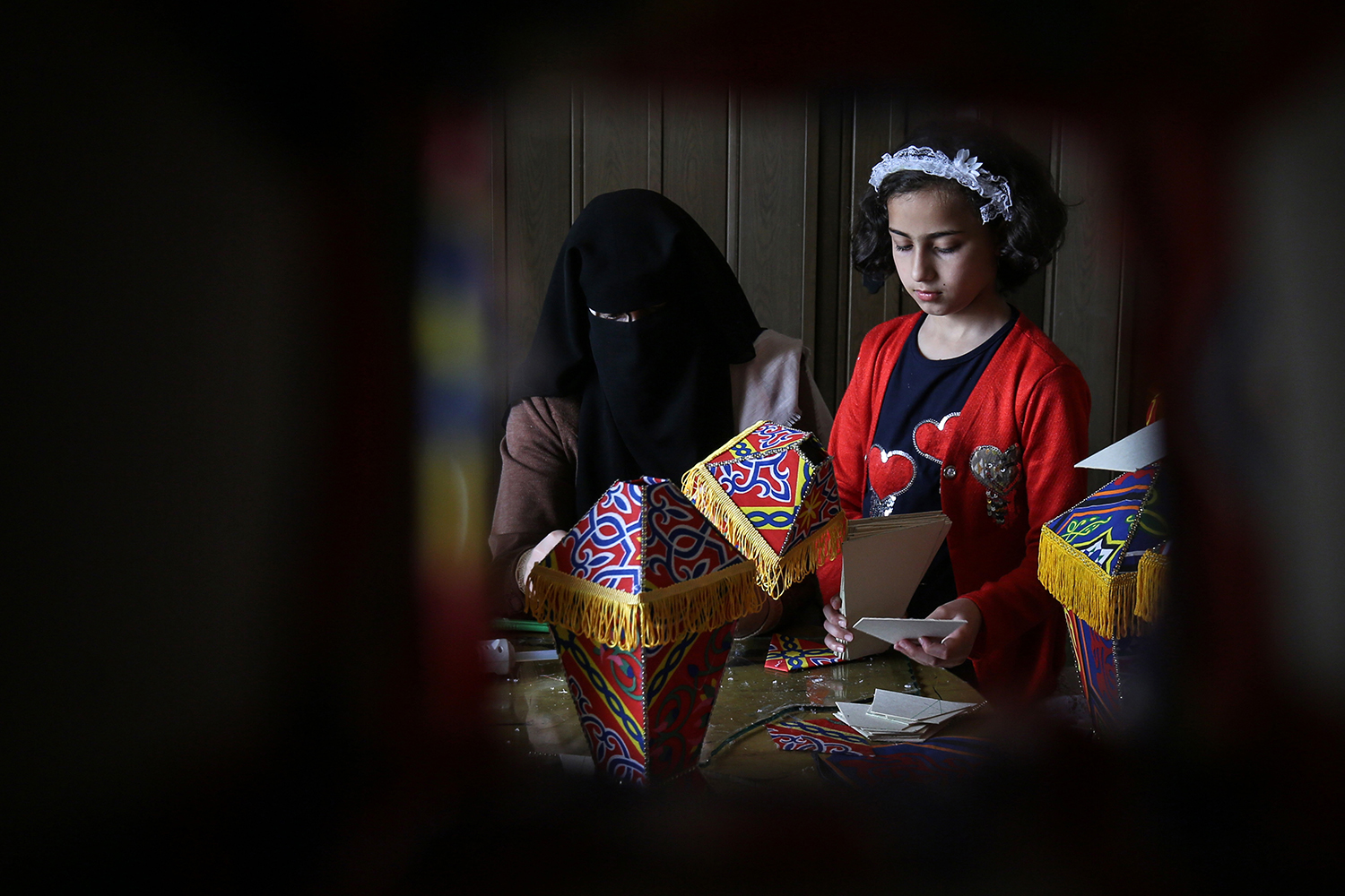 Members of the Palestinian al-Yaqoubi family gather around a table to make lanterns in Khan Yunis, a city in the southern Gaza Strip, on April 15. The family plans to sell the lanterns ahead of the Muslim holy month of Ramadan. SAID KHATIB/AFP via Getty Images