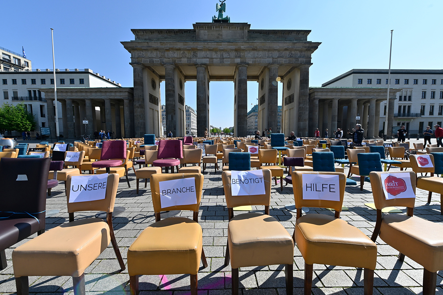 "Empty chairs with notes reading ""Our business needs help"" stand in front of Berlin's Brandenburg Gate during a protest of gastronomers on April 24."