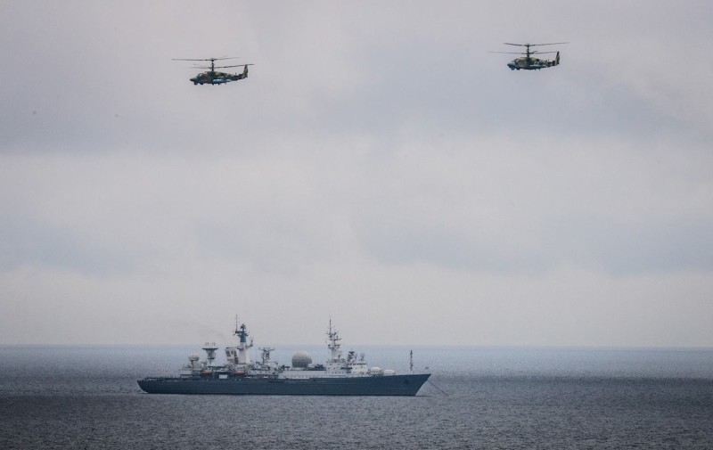 Two helicopters fly over the landing command ship during the Vostok-2018 military drills at Klerka training ground on the Sea of Japan coast on Sept. 15, 2018.
