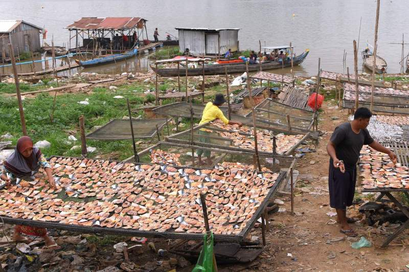 Cambodians dry fish in a village along the Tonle Sap River in Phnom Penh in 2019, the year the country faced one of the worst droughts in modern history.
