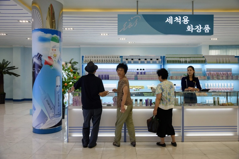 Customers look at makeup products in a store attached to a cosmetics factory in Pyongyang on July 28, 2018.