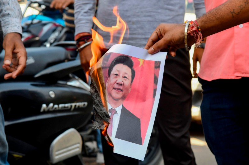 Indian activists burn a photograph of Chinese President Xi Jinping as they protest against his visit in India, in Guwahati on Oct. 11, 2019.