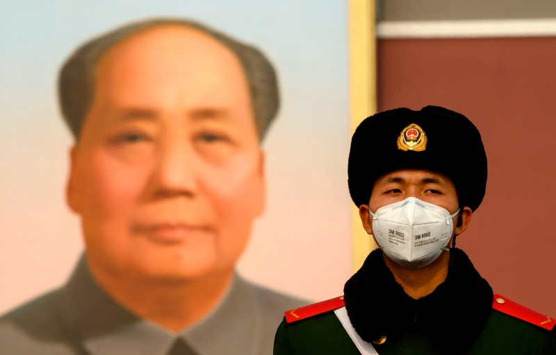 A paramilitary police officer stands guard in front of a portrait of Mao Zedong at the Tiananmen Gate in Beijing on Jan. 28.