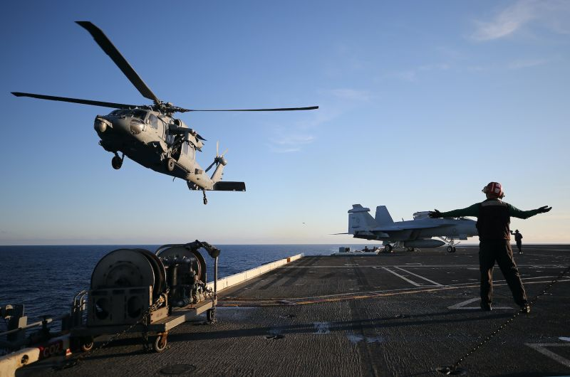 A U.S. Navy helicopter lands on an aircraft carrier.