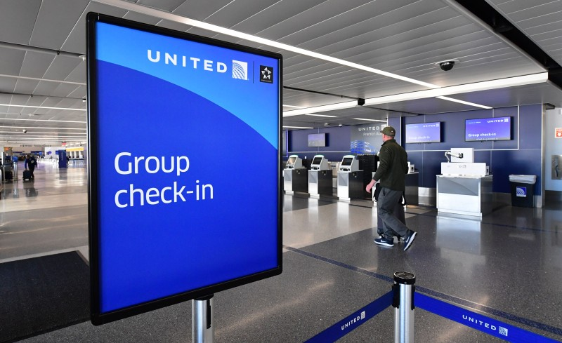 A man arrives with his luggage at a nearly deserted United Airlines check-in counter at Los Angeles International Airport on March 18.