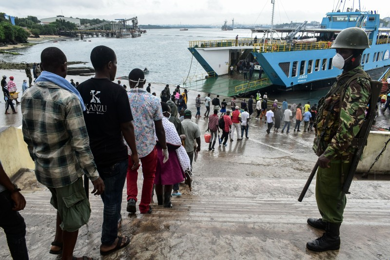 Commuters stand in a line to curb the spread of the coronavirus as they proceed to board a ferry at the Likoni ferry terminal in Mombasa, Kenya, on March 27.