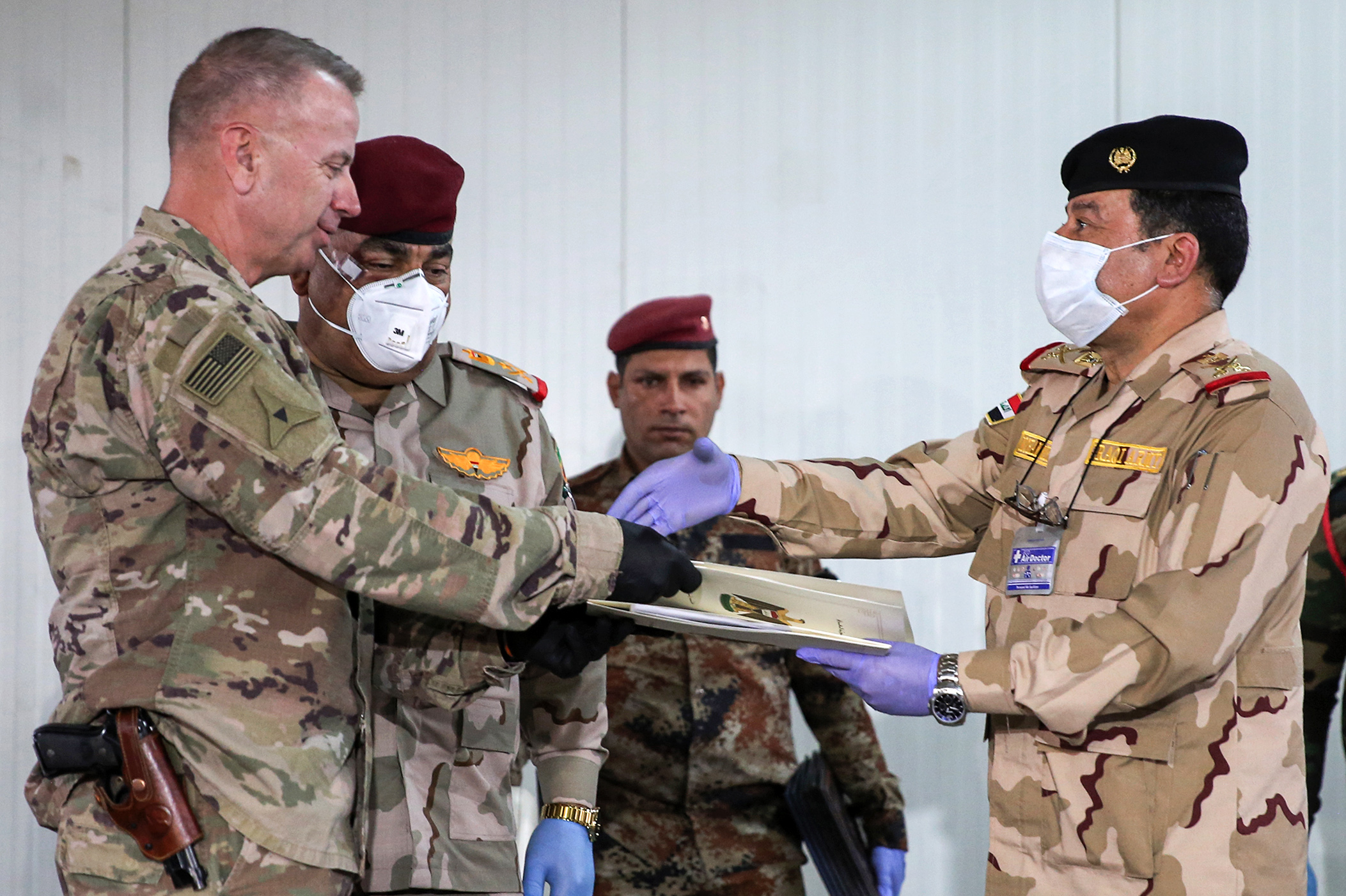 U.S. Army Brig. Gen. Vincent Barker (left) exchanges documents and shakes hands with Iraqi Staff Maj. Gen. Mohammad Fadhel Abbas, both wearing protective gear as a safety measure during the coronavirus pandemic, during a handover ceremony at the K1 air base in northern Iraq on March 29.