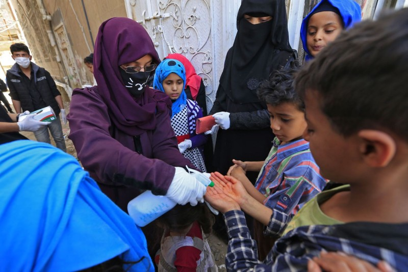 A Yemeni volunteer sprays disinfectant on the hands of kids in one of Sanaa's impoverished neighborhoods, on March 30, amid concerns of a coronavirus outbreak.