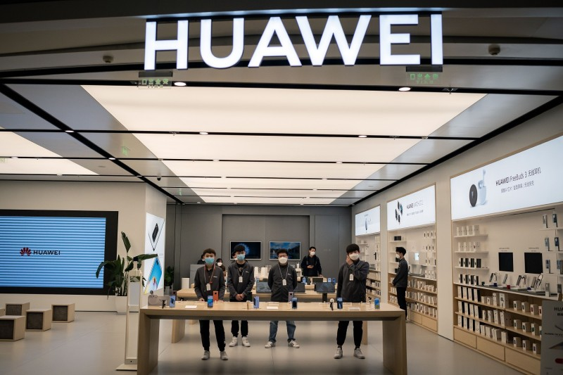 Workers wait for customers inside of a Huawei shop in Beijing on April 1