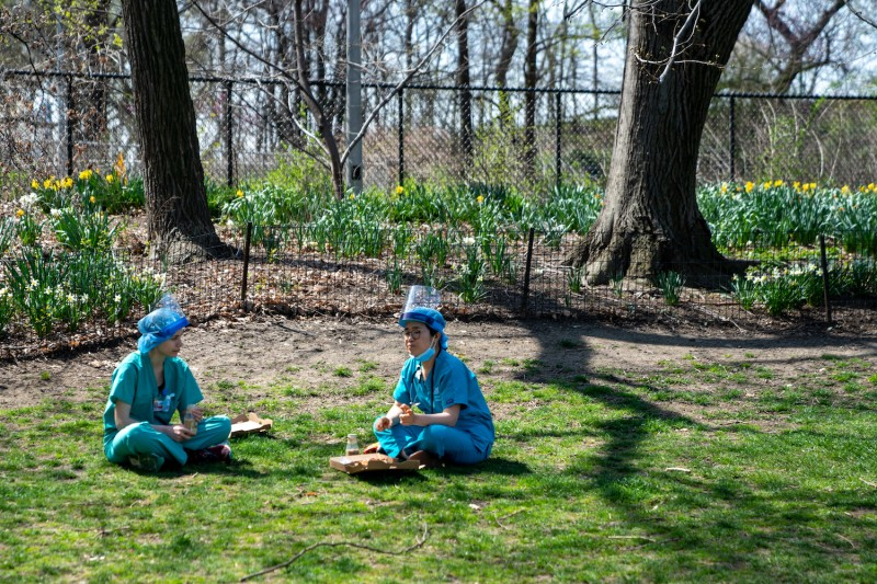 Two nurses have lunch on the grass in Central Park across from Mount Sinai hospital on April 7, 2020 in New York City, New York.