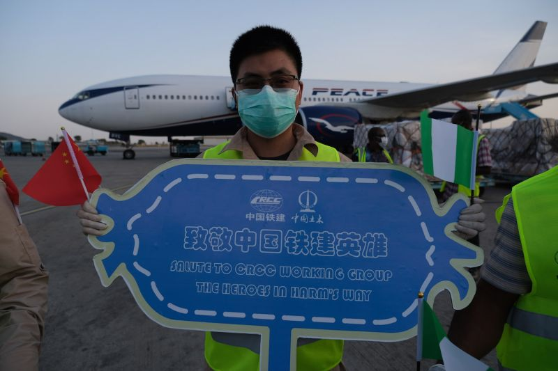 A man wearing a face mask holds a welcome sign at the Nnamdi Azikiwe International Airport in Abuja, on April 8, as a team of Chinese medics sponsored by China Railway Construction Corp. arrived in Nigeria to help fight the coronavirus pandemic.