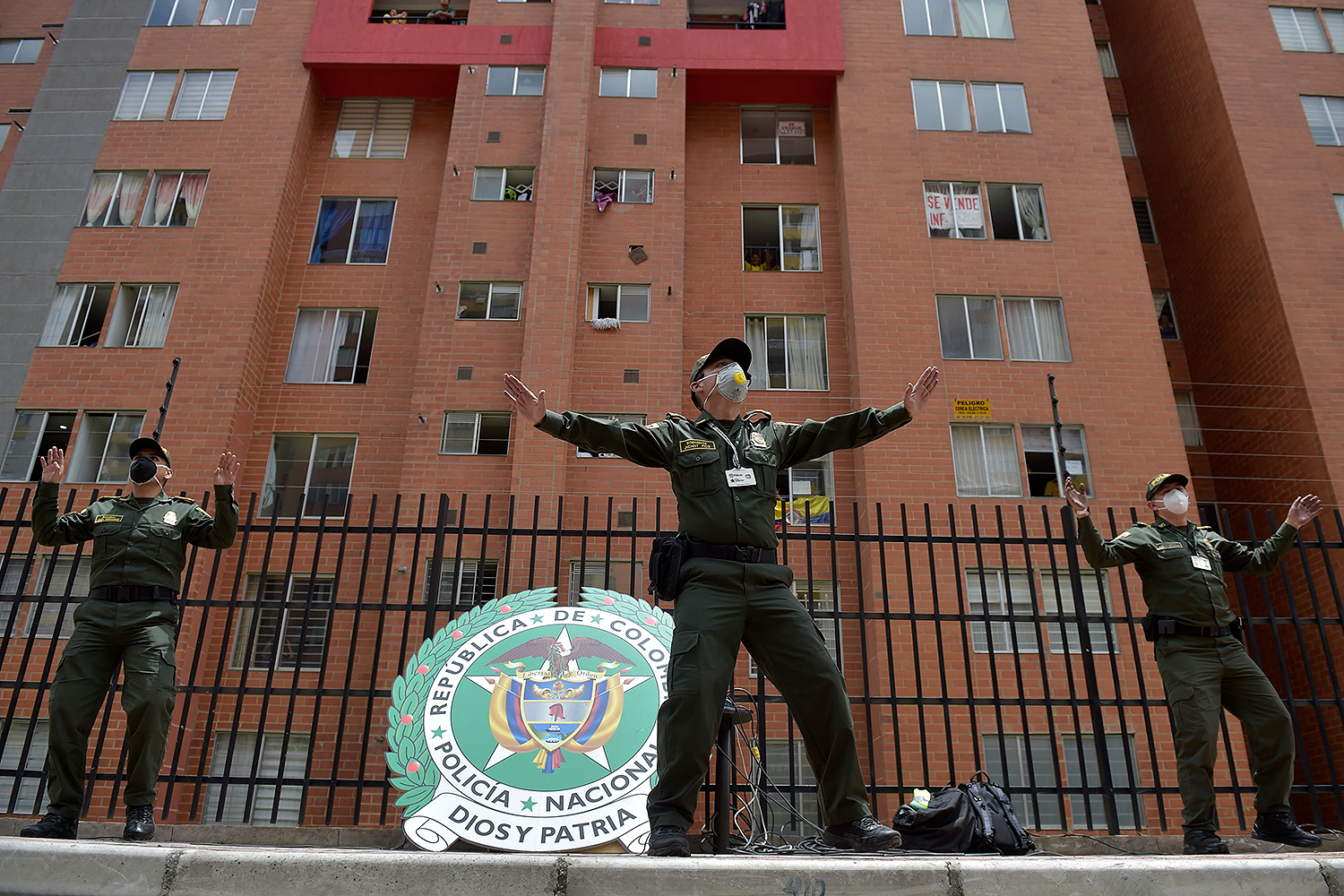 In an effort to cheer residents up during a government lockdown, police officers in Bogota, Colombia, encourage people to dance with them from their balconies and windows April 8. RAUL ARBOLEDA/AFP via Getty Images
