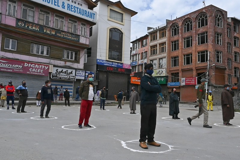 People maintain social distance as Indian paramilitary personnel distribute food for those in need during the government-imposed nationwide lockdown in Srinagar, Jammu and Kashmir, on April 9.