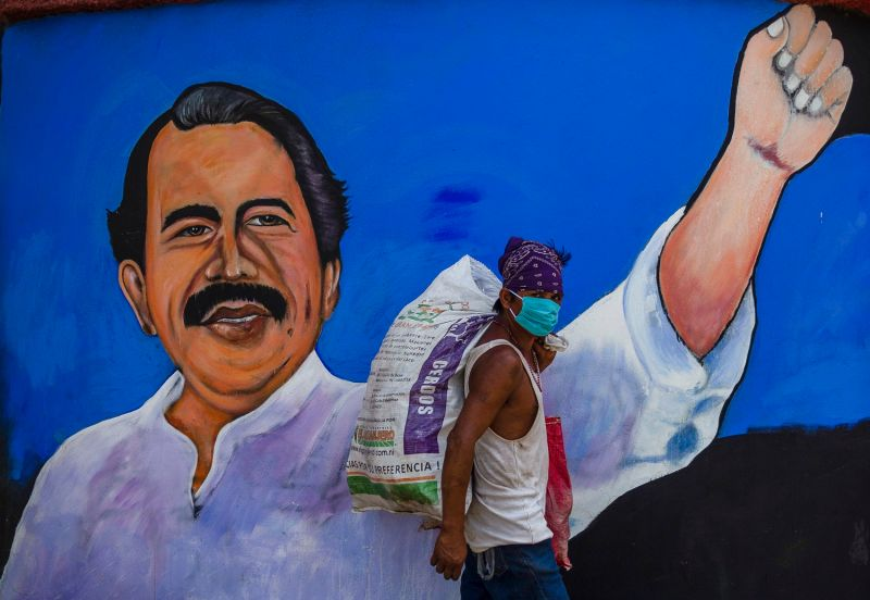 A man wears a face mask as he walks past a mural depicting Nicaraguan President Daniel Ortega in Managua on April 9.