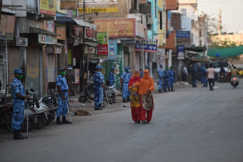 Muslim women walk in front of paramilitary personnel during a government-imposed nationwide lockdown as a preventive measure against the coronavirus in Ahmedabad, India, on April 12.