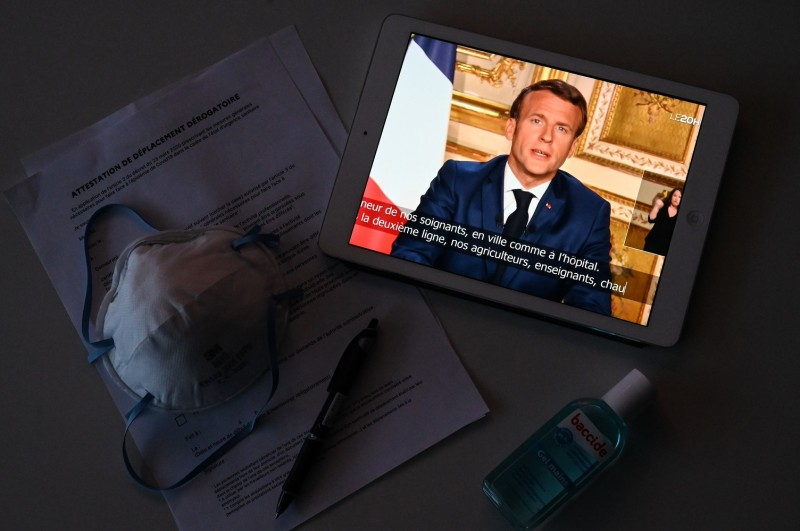 French President Emmanuel Macron is seen on a tablet screen in Montpellier, southern France, as he speaks from the Élysée Palace in Paris during a televised address to the nation on April 13.
