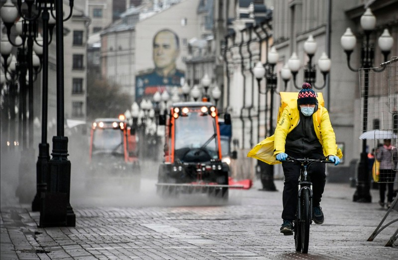 A food delivery courier cycles as municipal vehicles clean and disinfect the area, with a building decorated with a mural depicting Soviet WWII commander Marshal Georgy Zhukov in the background, in downtown Moscow on April 14.