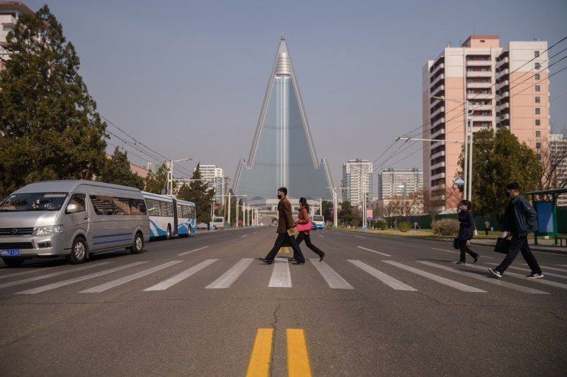 People wearing face masks walk across a street before the Ryugyong hotel in Pyongyang on April 15.