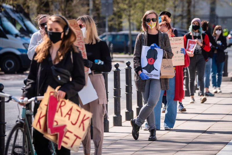 Women's rights activists protest against a draft legislation that would ban the abortion of fetuses with congenital birth defects, in front of the parliament building in Warsaw, on April 16, while observing coronavirus safety measures.